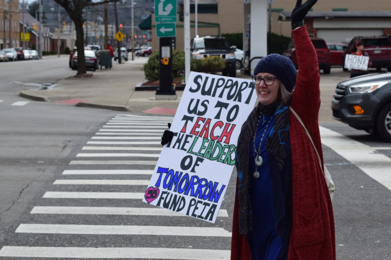 Teachers outside on 5th Avenue of Huntington, West Virginia holding signs calling for increased pay raises and lower deductibles and insurance rates.