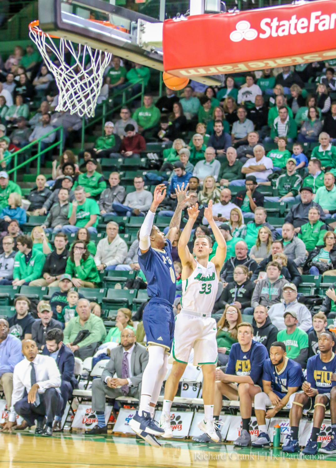 Marshall guard Jon Elmore (33) shoots a 3-pointer around an FIU defender during their matchup in the 2017-18 season. Elmore's shooting from beyond the arc is a staple in Marshall's offense.
