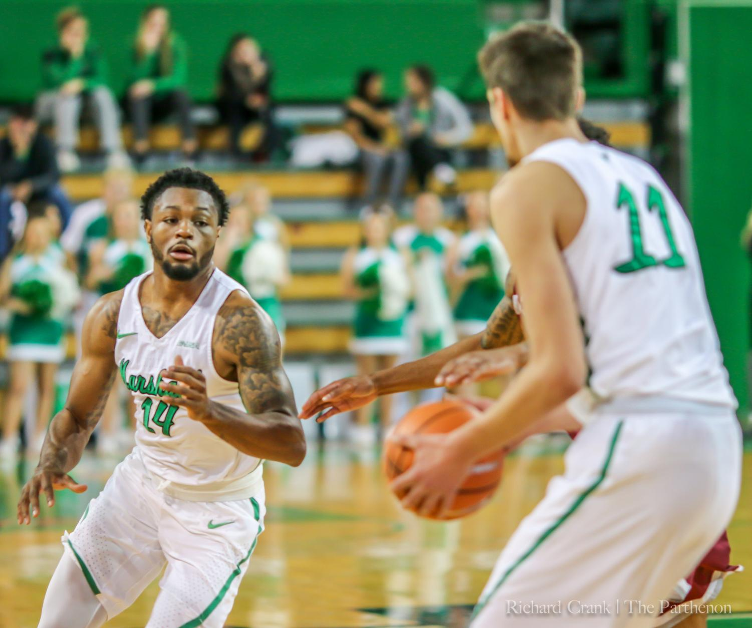 Junior guard C.J Burks prepares to reviece a pass from junior forward Ajdin Penava. Burks continues his five-game streak of leading the Herd in total points scored, as he comes off a 29-point scoring performance against  Western Kentucky.