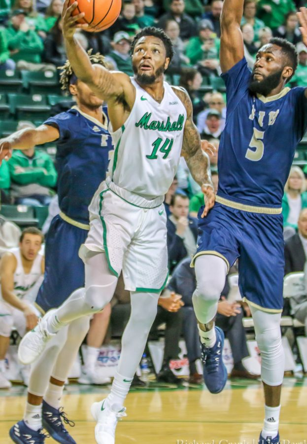 Marshall+guard+C.J.+Burks+%2814%29+drives+past+FIU+guard+Eric+Lockett+in+a+game+during+the+2017-18+season.