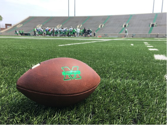 Marshall football proceeds with one of its with spring practices last seasson in the background of an official Marshall practice ball. The Herd practices at either Joan C. Edwards Stadium or the Chris Cline Athletic Complex (depending on weather) as media, season ticket holders and Big Green members are permitted to spectate.