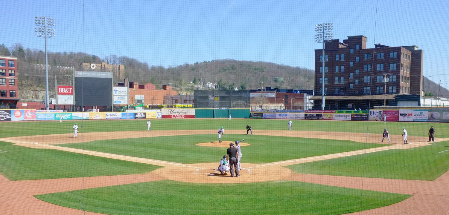 Marshall, sporting home white jerseys, plays defense as it attempts to stifle Florida Atlantic in game one of its Saturday afternoon doubleheader in Charleston, West Virginia. The Herd plays its C-USA matchups at Appalachian Power Park, which is also home of the Pittsburgh Pirates' minor league affiliate, the West Virginia Power.