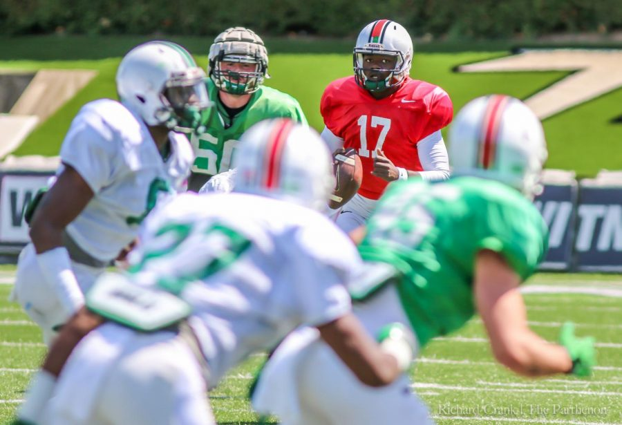 Quarterback Isaiah Green (17, in red jersey) looks downfield for an open receiver during the Green-White game. Green completed 80 percent of his passes and had two touchdowns in the game.