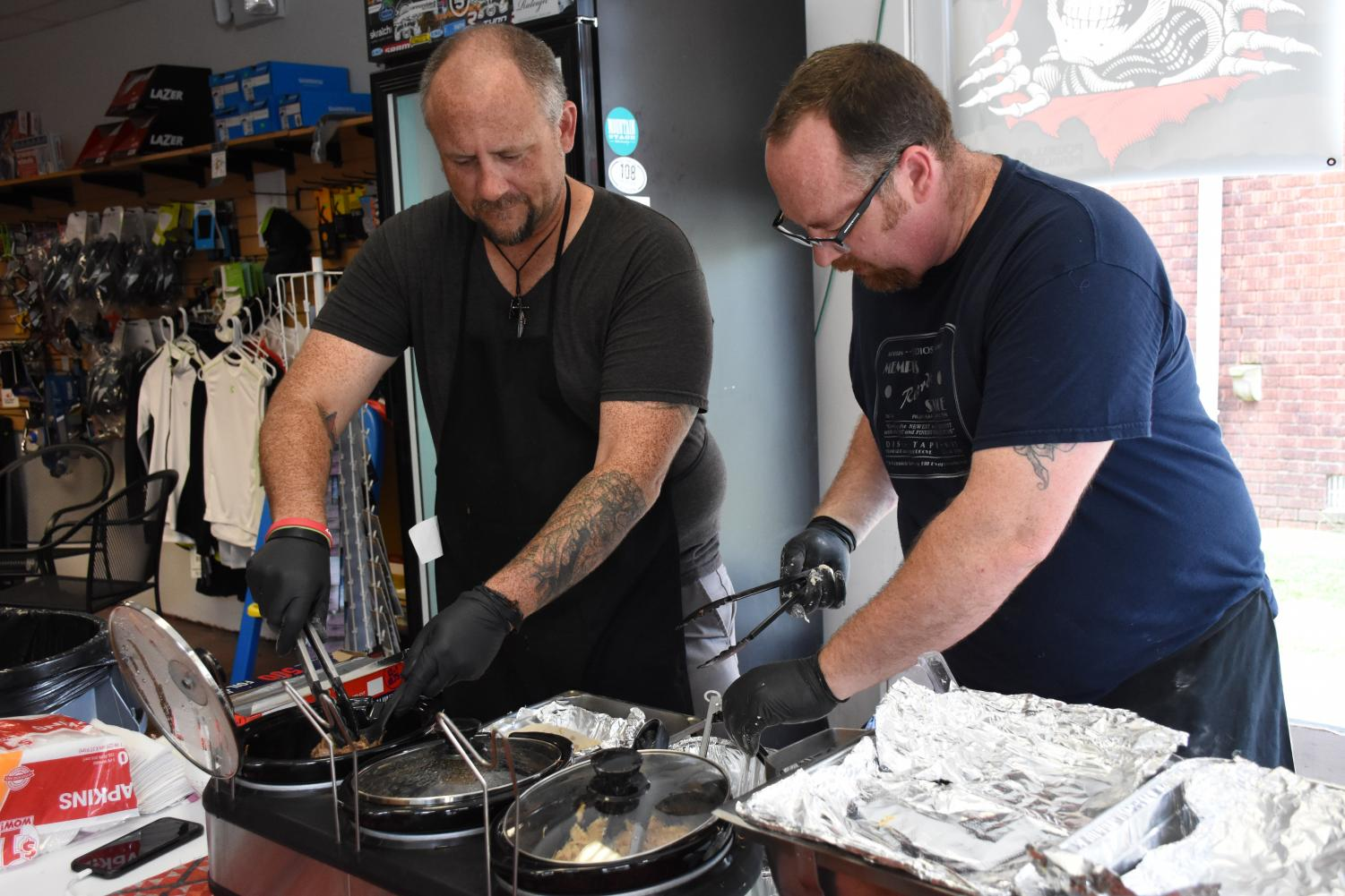 Tim Watson (left) and Chris Wood (right) preparing a buffalo taco at their pop-up shop at Huntington Cycle and Sport.