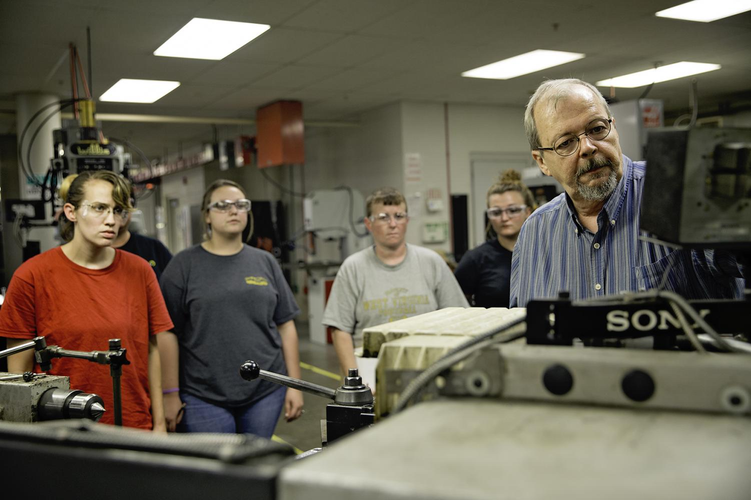 Machinist instructor Rick Smoot, right, demonstrates the proper use of a digital readout screen on the Clausing engine lathe for students in the Step Up for Women Pre-Apprenticeship Program at RCBI.
