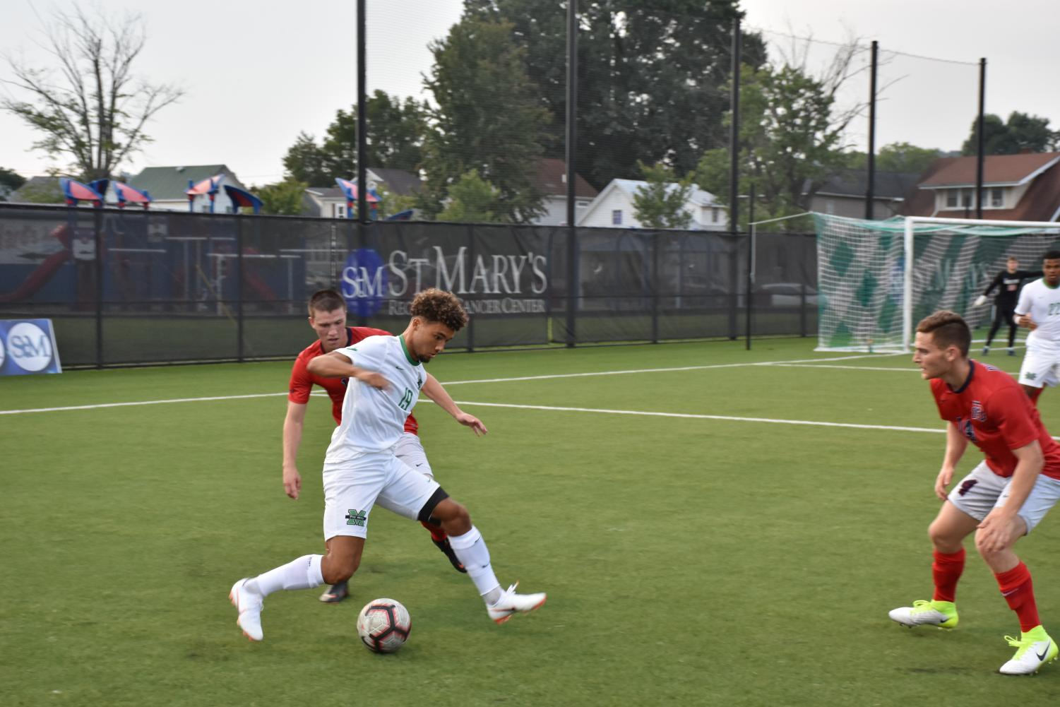 Freshman+midfielder+Charly+Borges+handles+the+ball+around+two+Duquesne+defenders.+