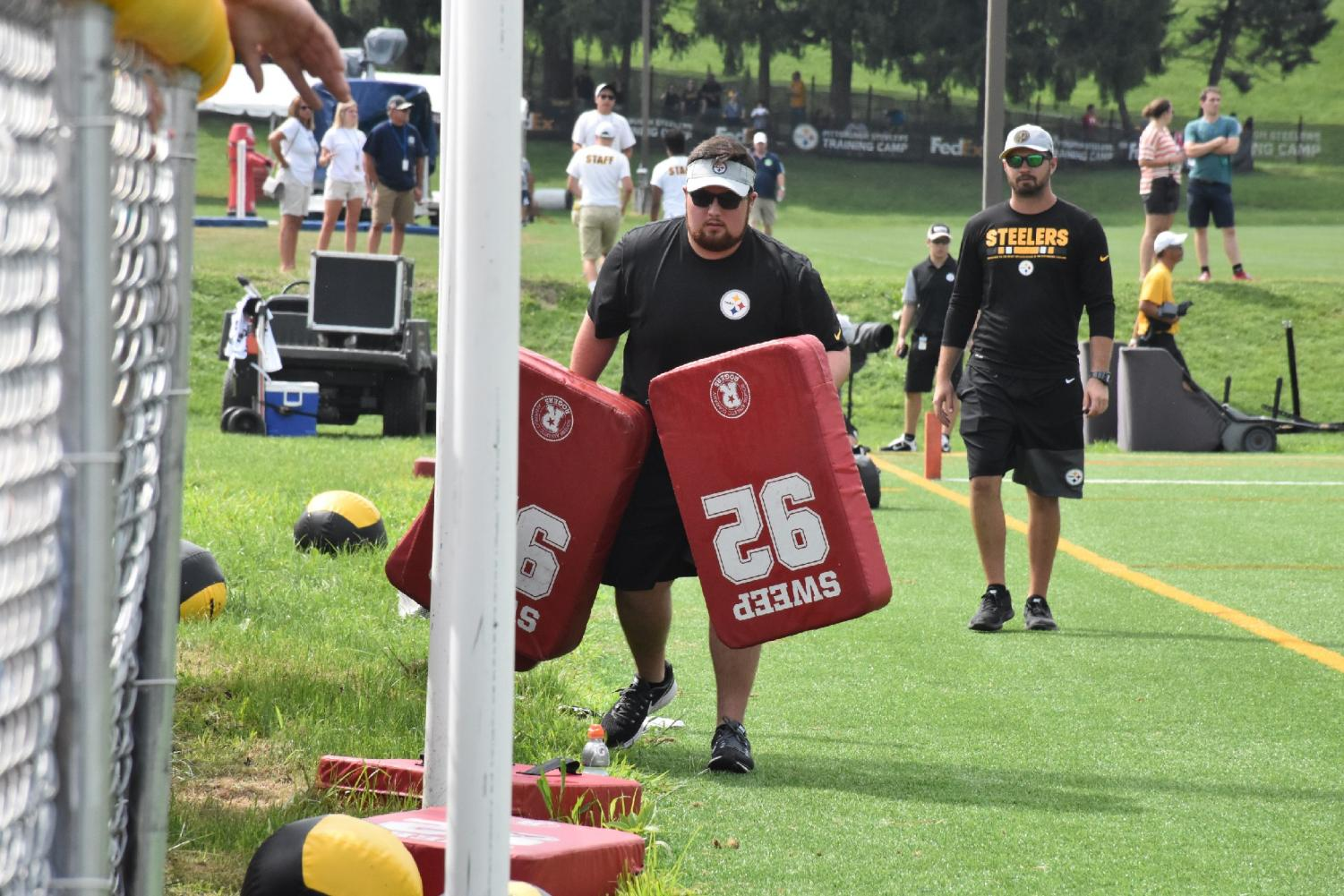 Kyle Powers (left) carries equipment at the Steelers' training camp as an assistant coach looks on. Powers has similar duties for Marshall's athletic program during the school year.