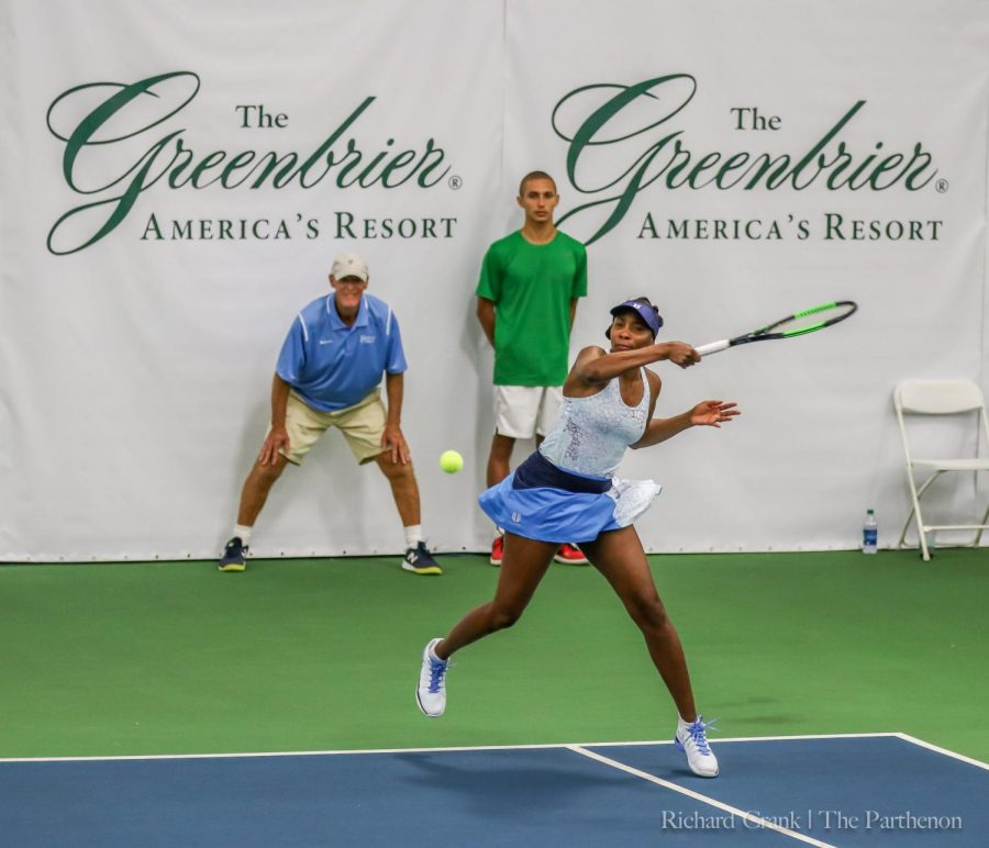 Venus Williams returns a ball in front of the Greenbrier logo.