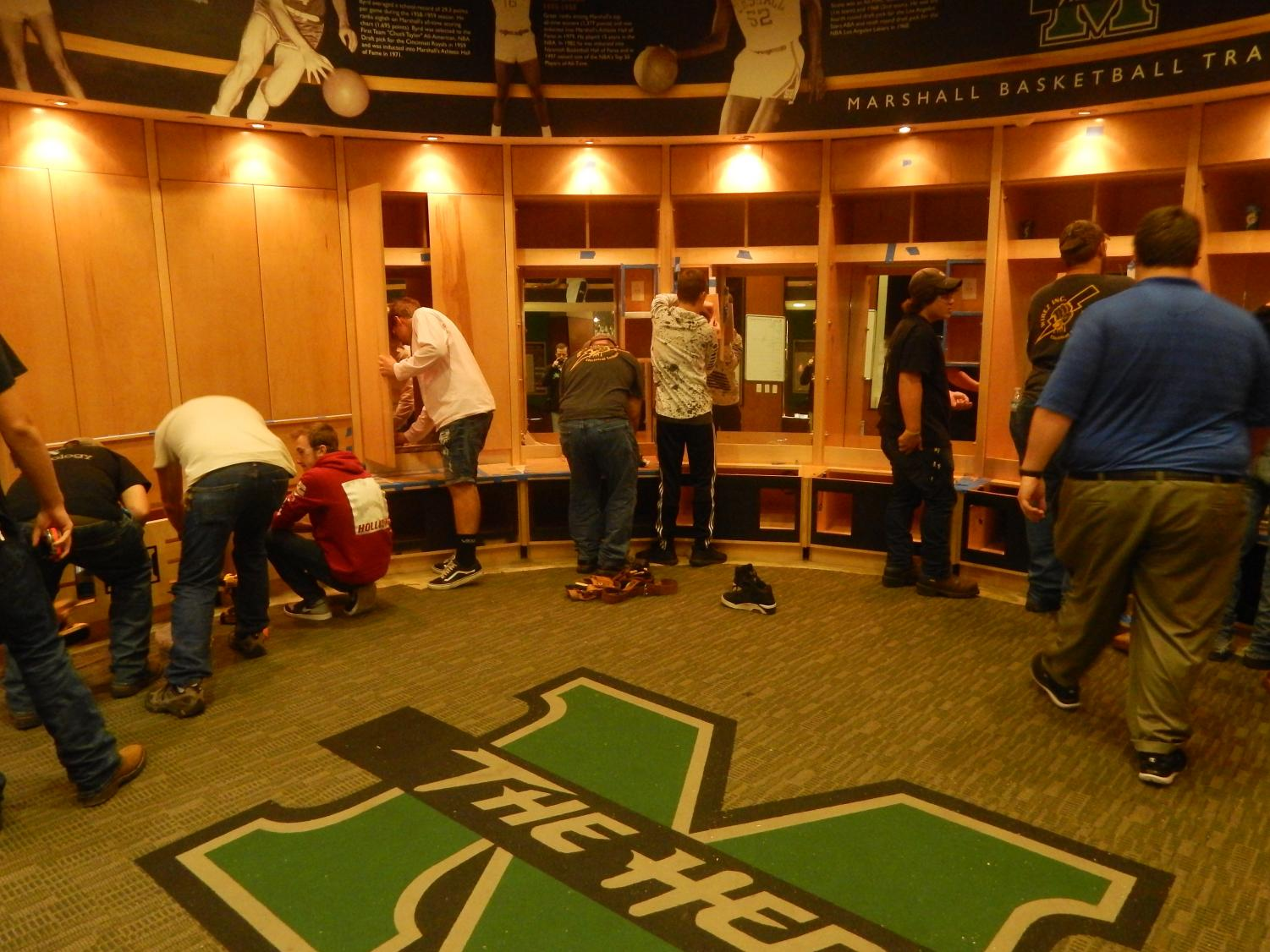 Local high school students work alongside their instructors in the Cam Henderson Center locker room. The instructors guide the students while they work hands-on.