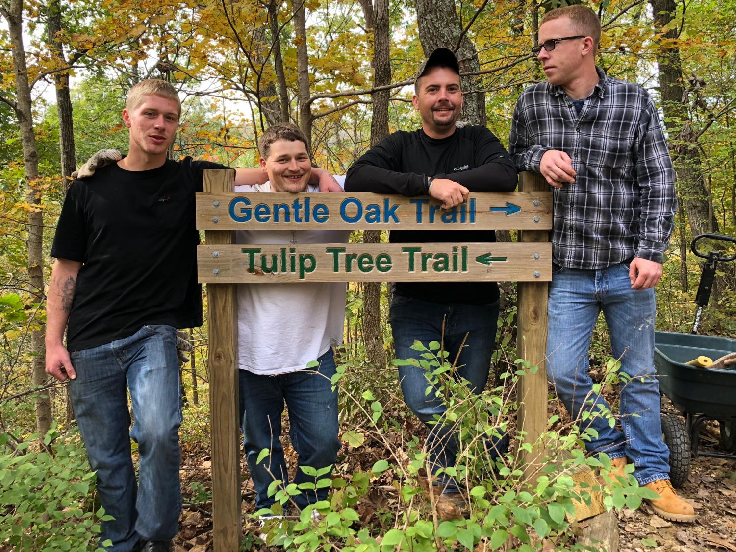 Tyler Webb (left) and fellow recovery point volunteers pose with trail signs, on a brief break from replacing hazardous steps on the paths.