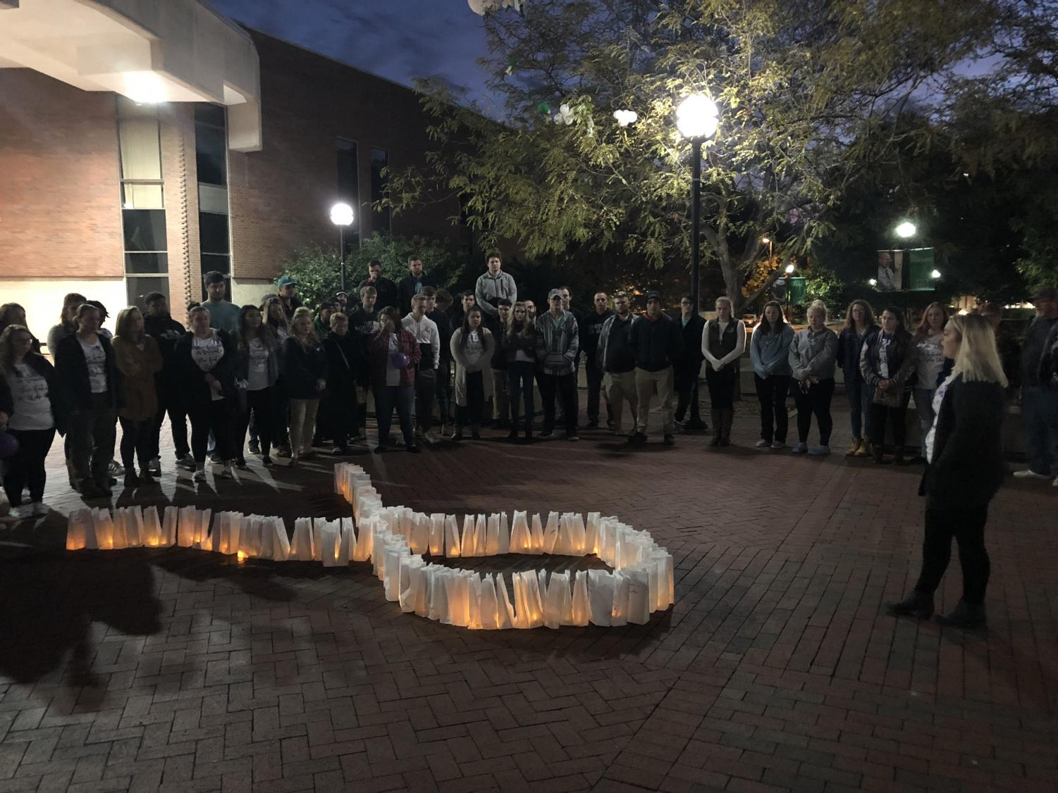 During the event on Thursday, Oct. 25, participants walked in silence around the Memorial Student Center plaza with candlelit bags just before placing them in the form of a ribbon to signify domestic violence awareness.