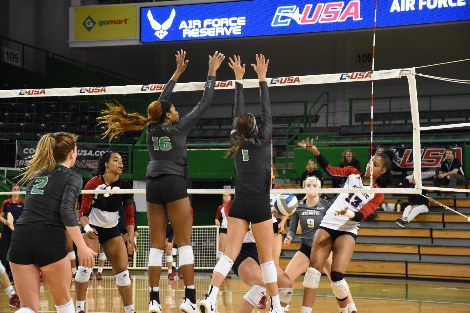 Senior middle blocker Jordyn Williams (left) and senior setter Karley York (right) combine to block on FAU attack in North Texas' quarterfinal win against the Owls.