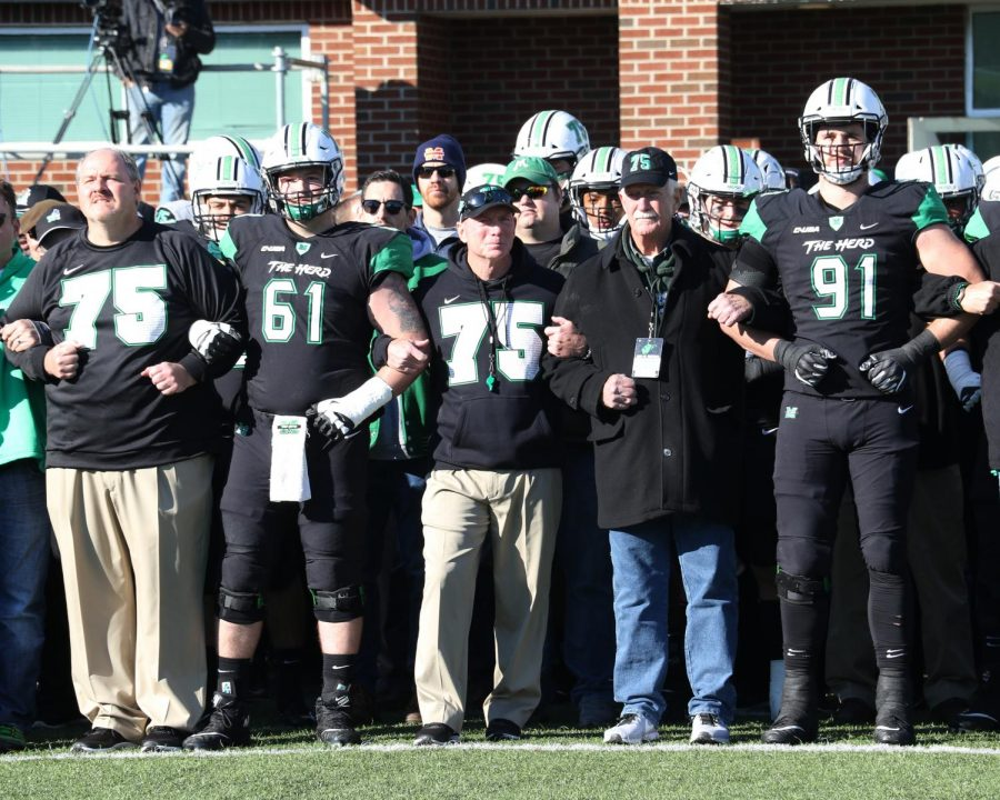 Marshall+head+coach+Doc+Holliday+stands+arm-and-arm+with+current+and+former+players+to+honor+the+75+who+died+in+the+1970+plane+crash.+The+Herd+honors+the+75+every+year+at+home+games.