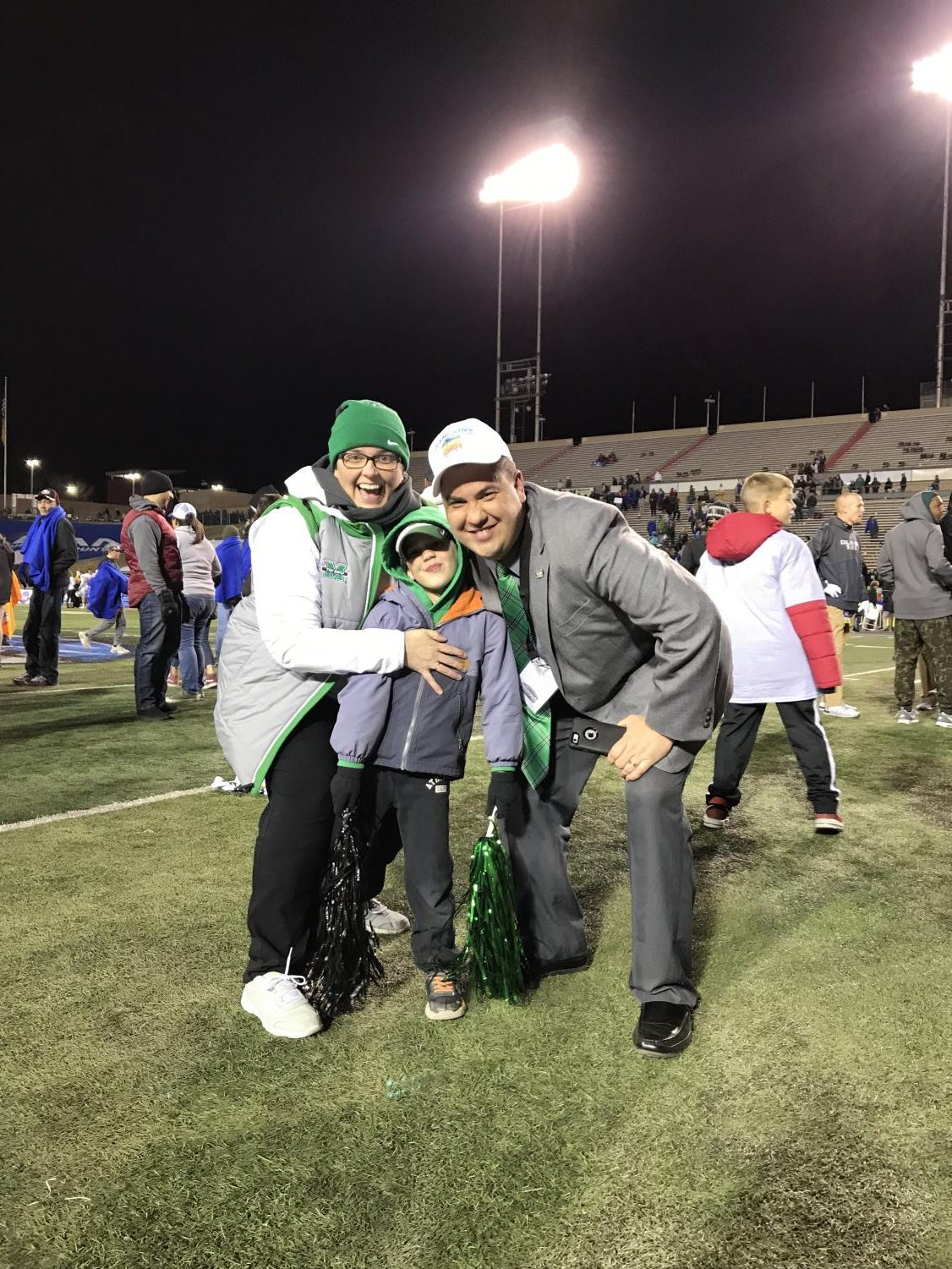 Kim Corriher, Gaffney Corriher and Jason Corriher (left-to-right) stand on the field of Dreamstyle Stadium after Marshall's 31-28 defeat of Colorado State in the Gildan New Mexico Bowl.