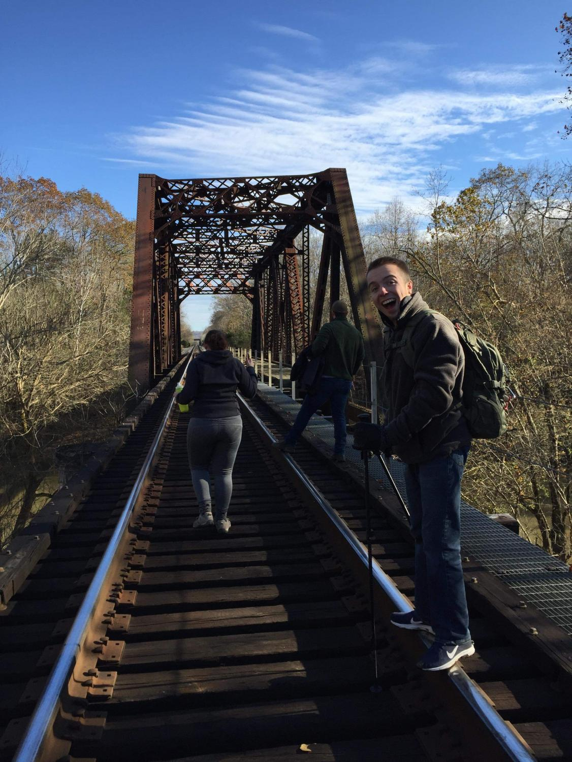 Kelsey Peters, Weston Wright and Josh Dehaven cross a bridge during Hiking Herd's recent hike at Barboursville Park.