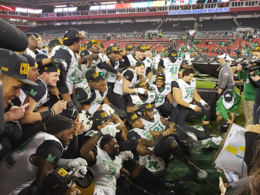Members of the Marshall football team pose for a postgame photo following Marshall's 38-20 win over South Florida in the Gasparilla Bowl.