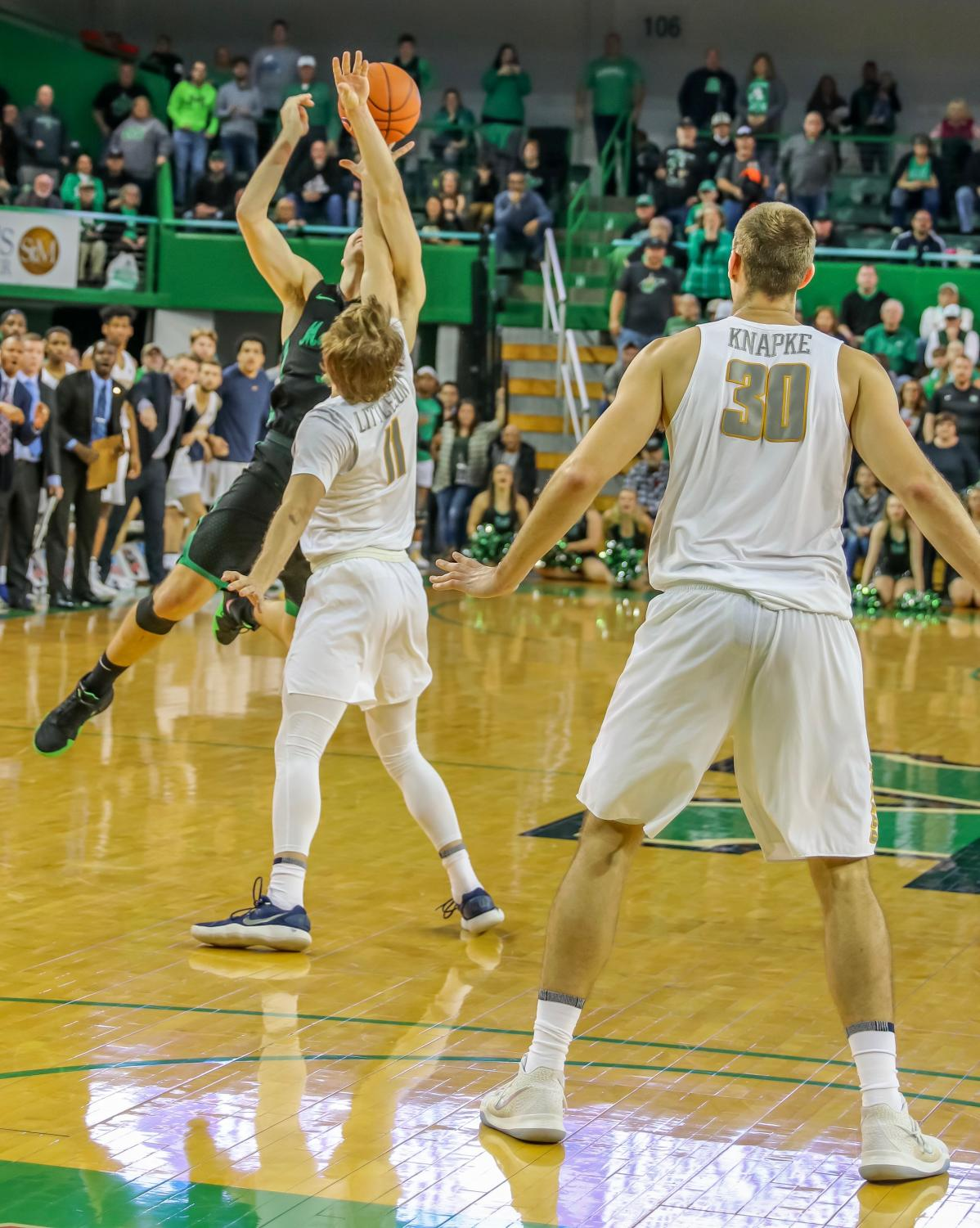 Herd senior guard Jon Elmore is defended by Toledo sophomore guard Spencer Littleson when attempting a crucial 3-point shot. The possible foul is not called and Elmore is unable to take free throws to secure a possible Marshall victory.