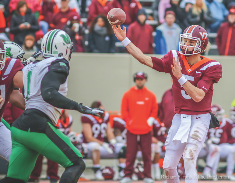 Virginia Tech redshirt junior quarterback Ryan Willis passes over Marshall's defense in the Hokies' 41-20 defeat of the Herd. Willis completes 18 of his 26 passes for 312 yards and four touchdowns.