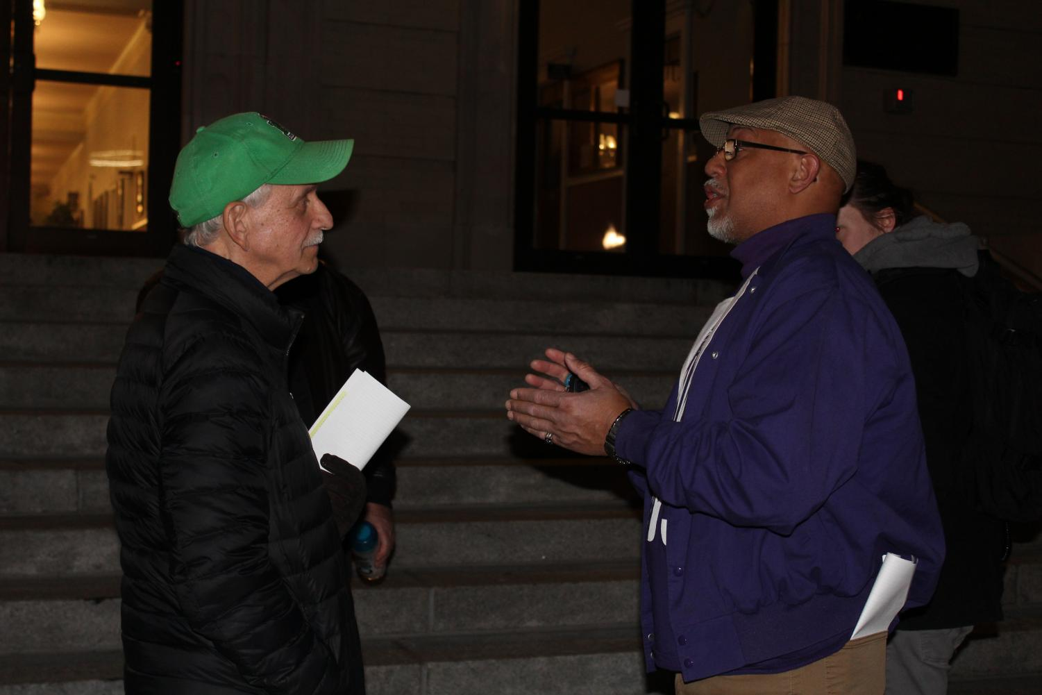 Huntington resident Mark Connelly talks with Damon Core, an executive board member of SEIU 1199, about the hospital board deal ordinance outside the Huntington City Council meeting.