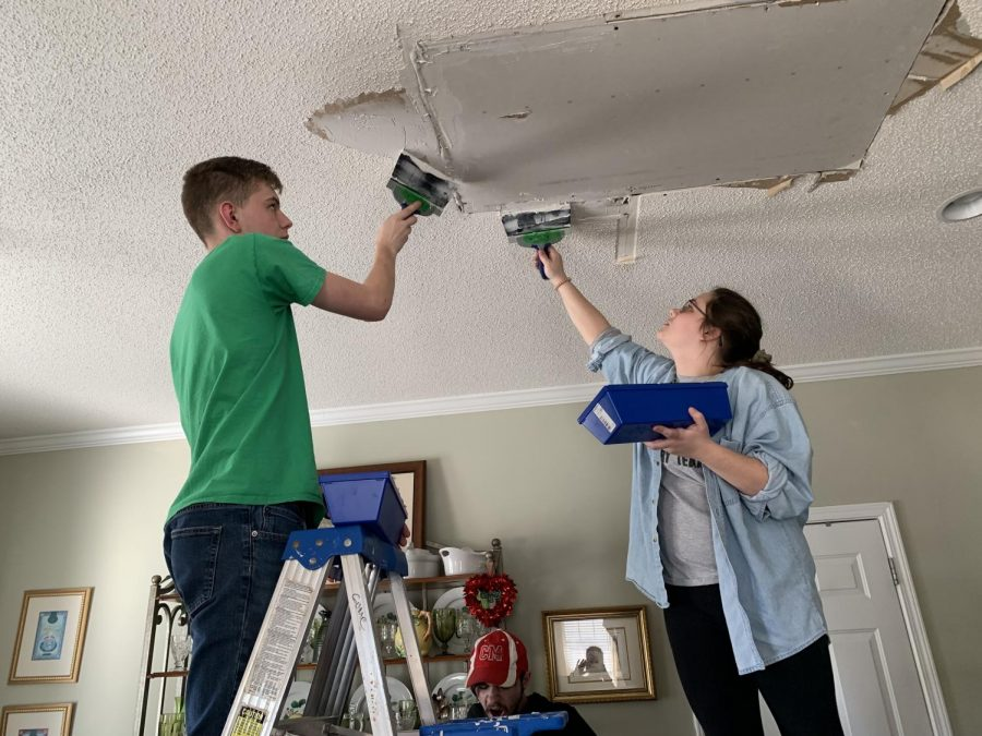 Freshman Gavin Boothe and junior Shyanna Hatten mud drywall where ceiling was damage from Hurricane Florence during a mission trip to Wilmington, North Carolina.