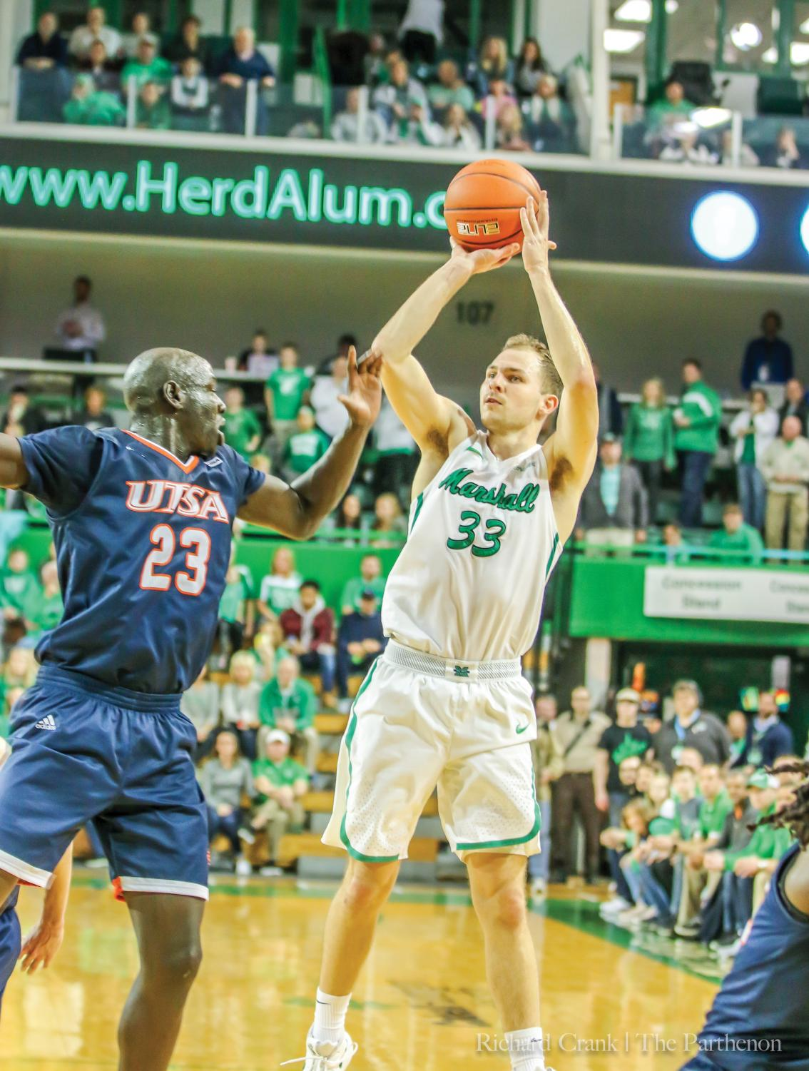 Marshall guard Jon Elmore (33) shoots a 3-pointer over UTSA's Atem Bier in the second half of the Herd's game against the Roadrunners on Feb. 2, 2019. Elmore made the shot and was fouled by Bior, setting up a four-point play to tie the game.