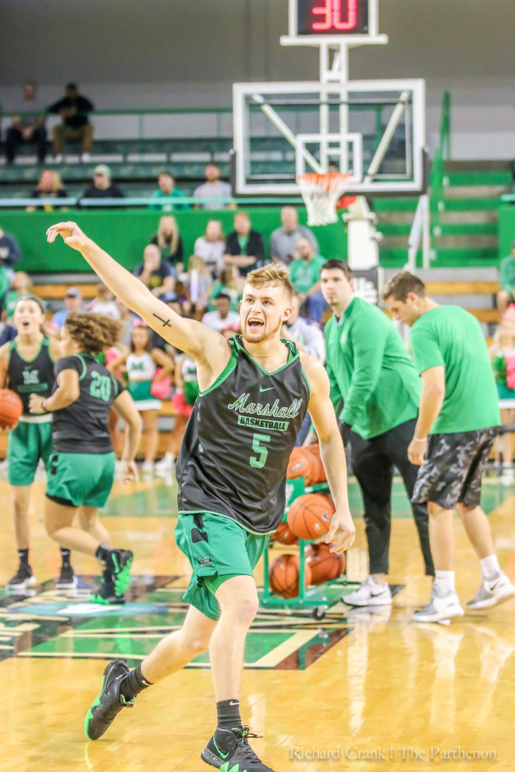 Marshall guard Jeremy Dillon (5) celebrates making a half-court shot at Herd Madness in October. Dillon is sitting out this season as a redshirt.