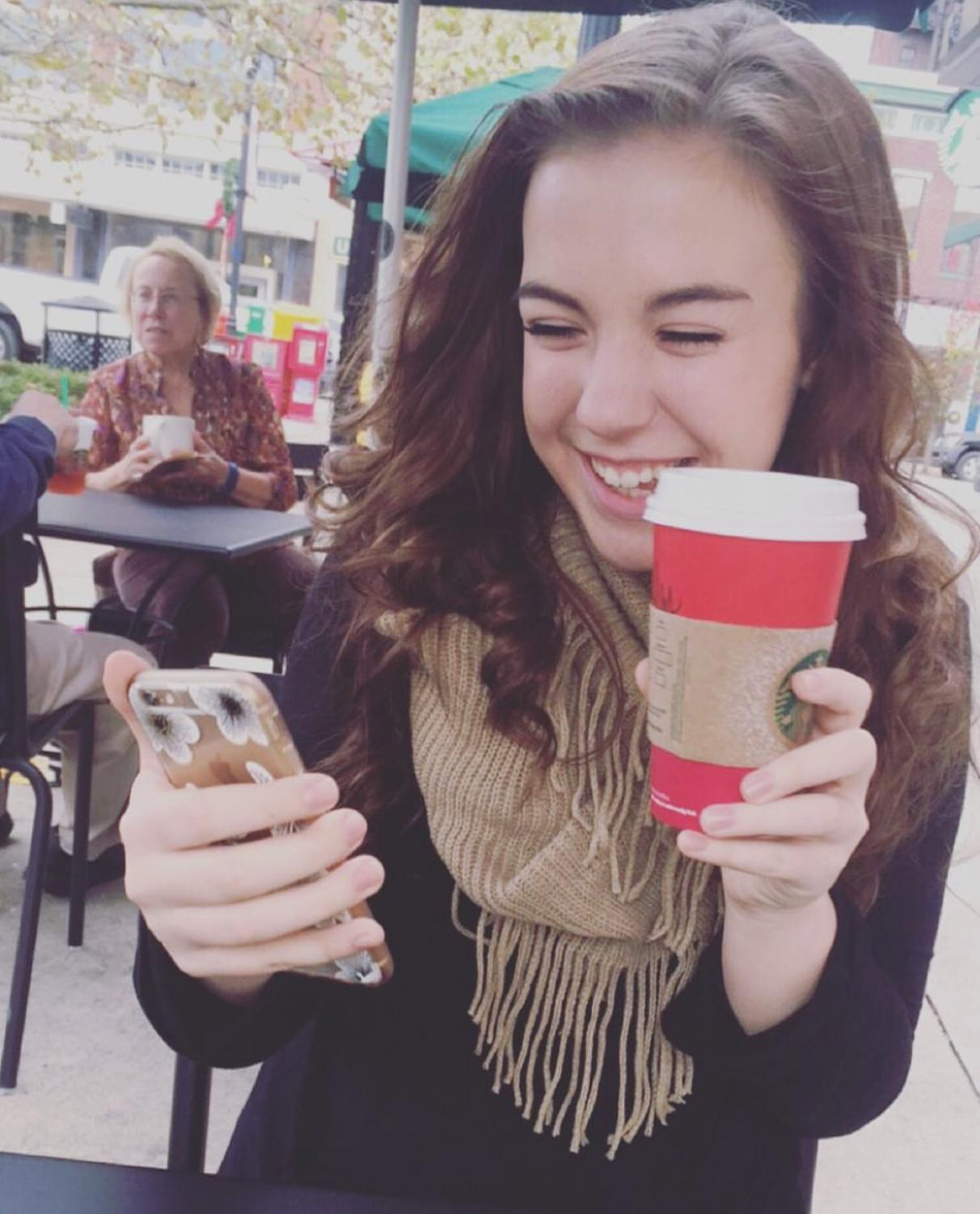 Rileigh Smirl smiles as she takes a picture with her coffee.