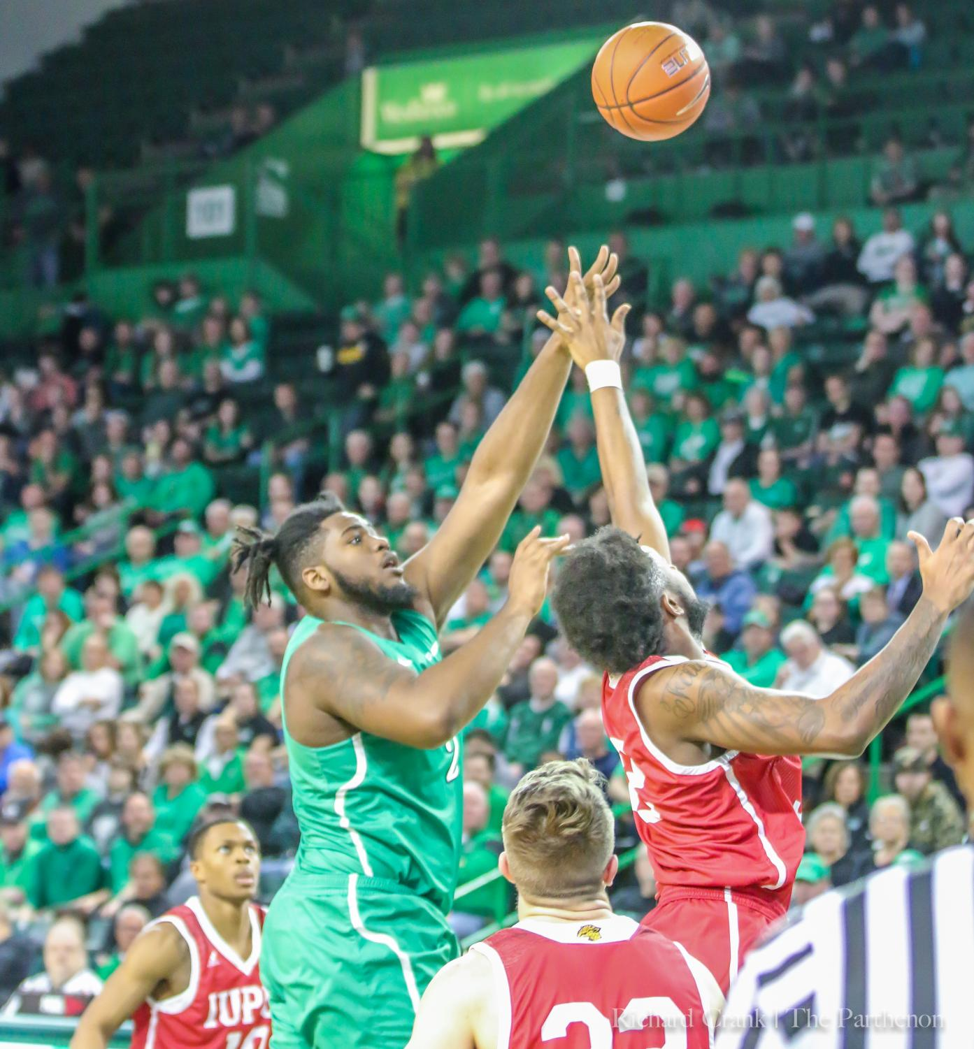 Marshall forward Iran Bennett (2) shoots a floater over IUPUI forward Elyjah Goss (32) in the first half of the Thundering Herd's game against the Jaguars on March 19, 2019.