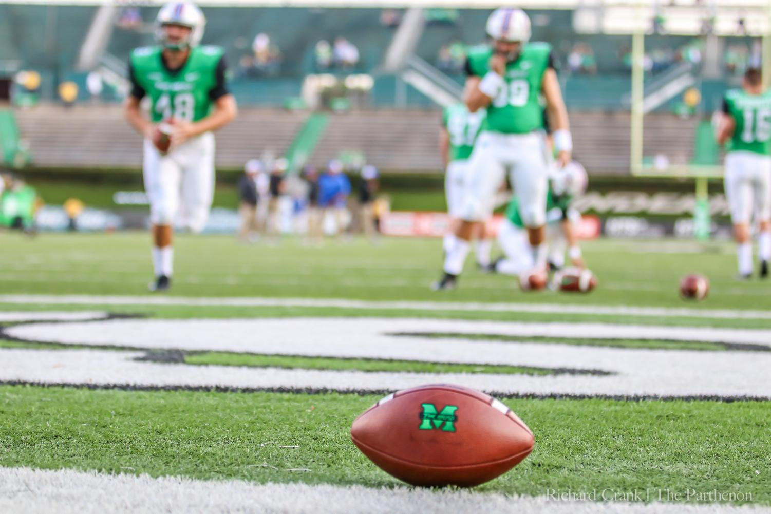 Prior to its game against Middle Tennessee, Marshall football specialists warm up in the background as a football remains in the end zone.