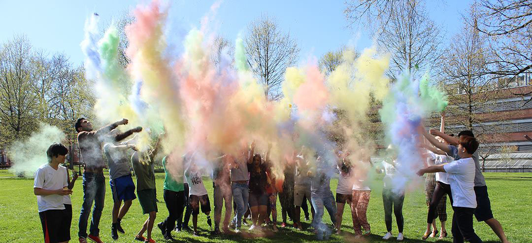 Students participate in Herd Holi in 2015 on Buskirk Field.