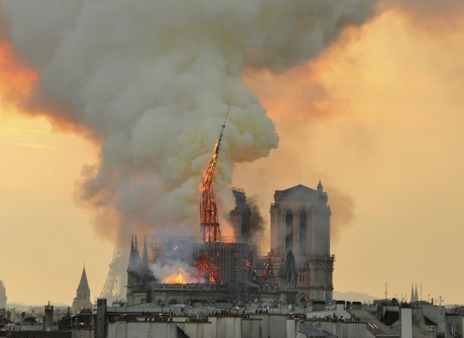 Flames and smoke rise from the blaze as the spire starts to topple on Notre Dame Cathedral in Paris, Monday, April 15.