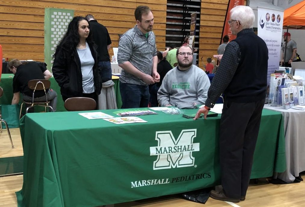 Third-year Marshall University medical students speak with an attendee of the 12th annual One4All Disability Expo, Saturday, April 6 at Huntington High School.