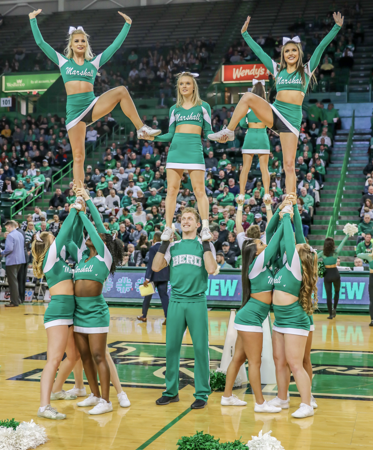 Marshall cheerleaders pose in a stunt before the men's basketball game versus UTEP on Jan. 31 in the Cam Henderson Center.