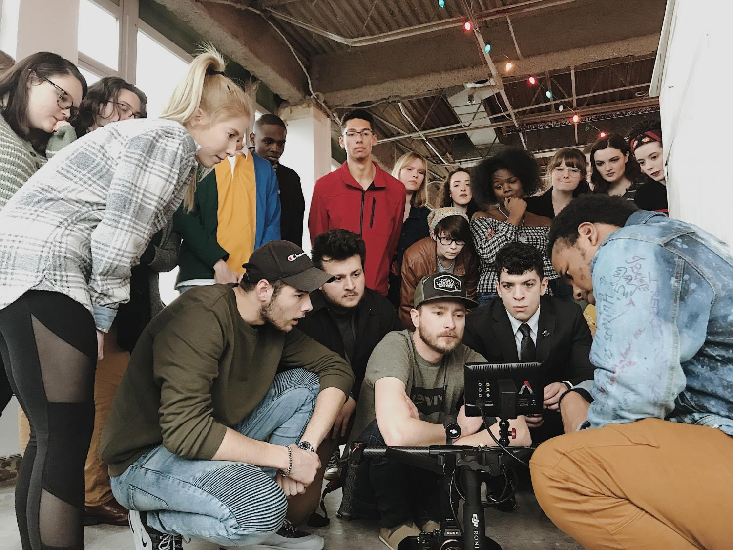 """""""Wake Up Dorothy"""" production team members gather around camera to make group decision."""