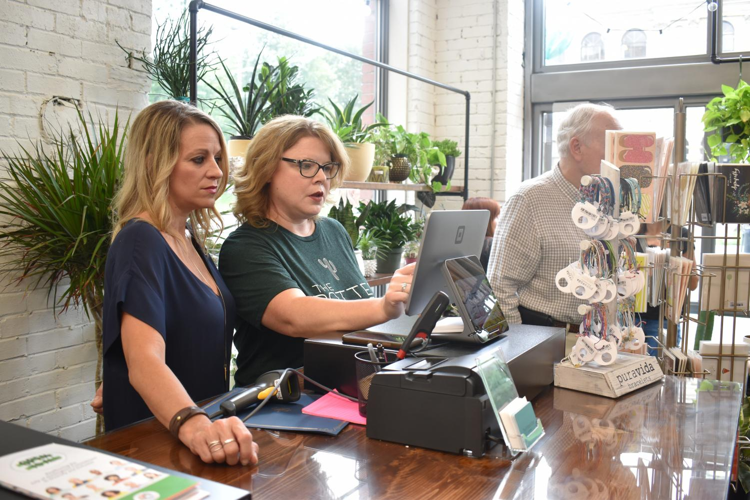 Wendy Canaday (right) and Lori Clary (left) working the register for their small business, The Potted Edge, in the progress building in downtown Huntington.