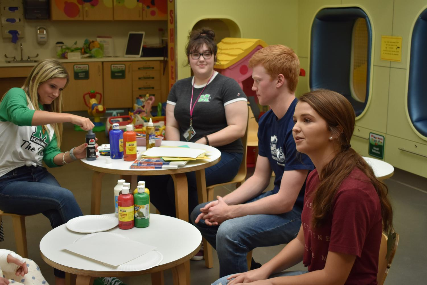 Marshall students Olivia Hart, Jodi Grimmett, Kaden Thomas and Caroline Foreman prep an activity with direction from one of the children.