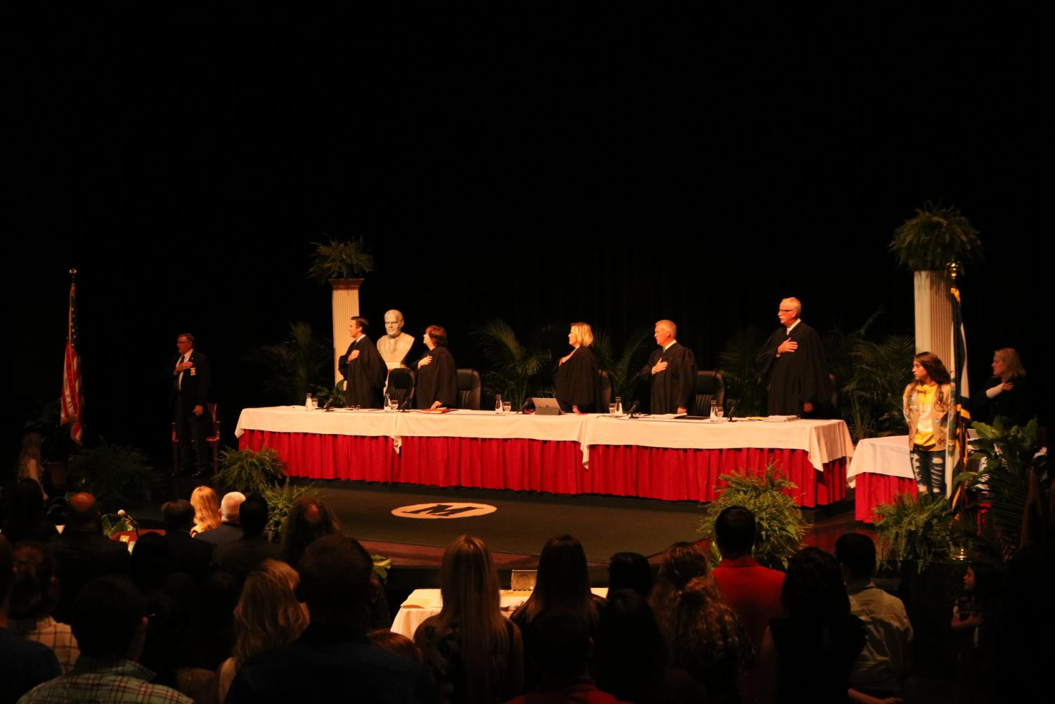 West Virginia Supreme Court Justice Evan H. Jenkins, Justice Margaret L. Workman, Chief Justice Elizabeth D. Walker, Justice Tim Armstead and Justice John A. Hutchinson pledge allegiance to the U.S. flag while meeting at the Joan C. Edwards Performing Arts Center to hear cases in front of a group of students and community members Sept. 11, 2019.
