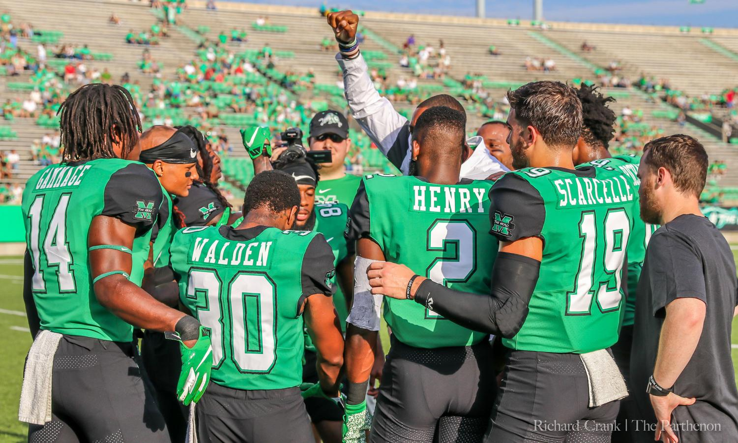 Members of the Marshall football team huddle together prior to the start of the game against VMI.