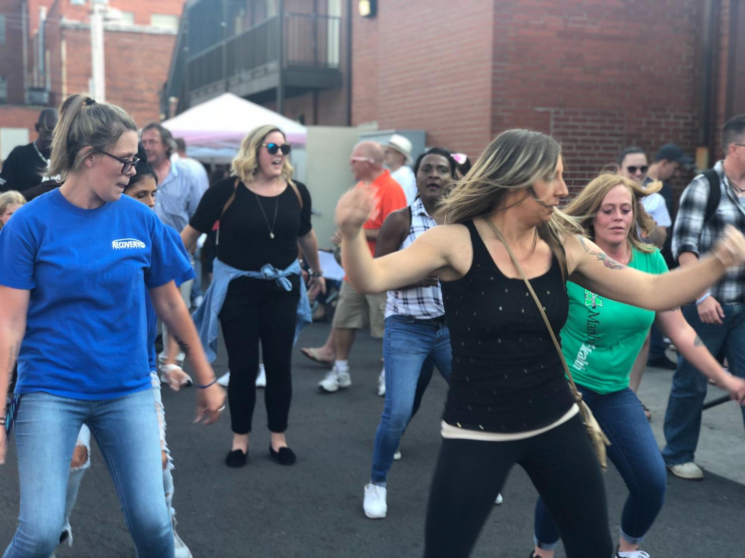 Local community members dance as part of celebrations Friday at Recovery Point's eighth annual Rally for Recovery in Huntington.