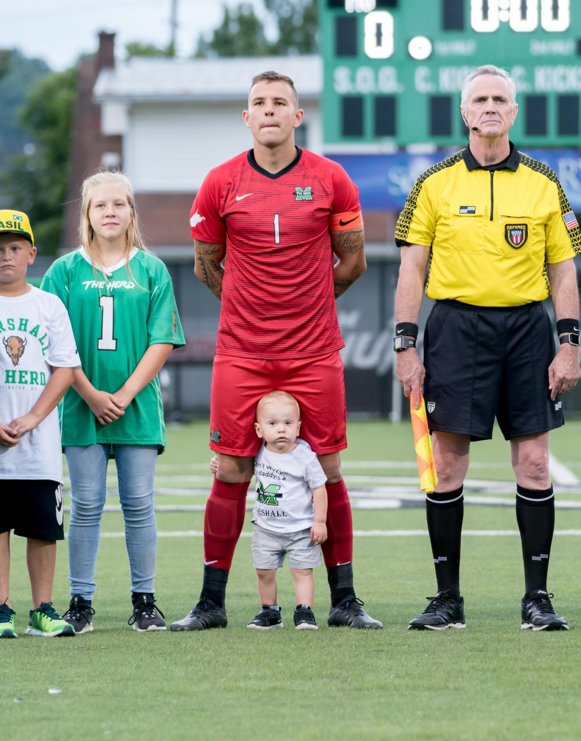 Paulo Pita and son Brody stand in line before the start of the game.