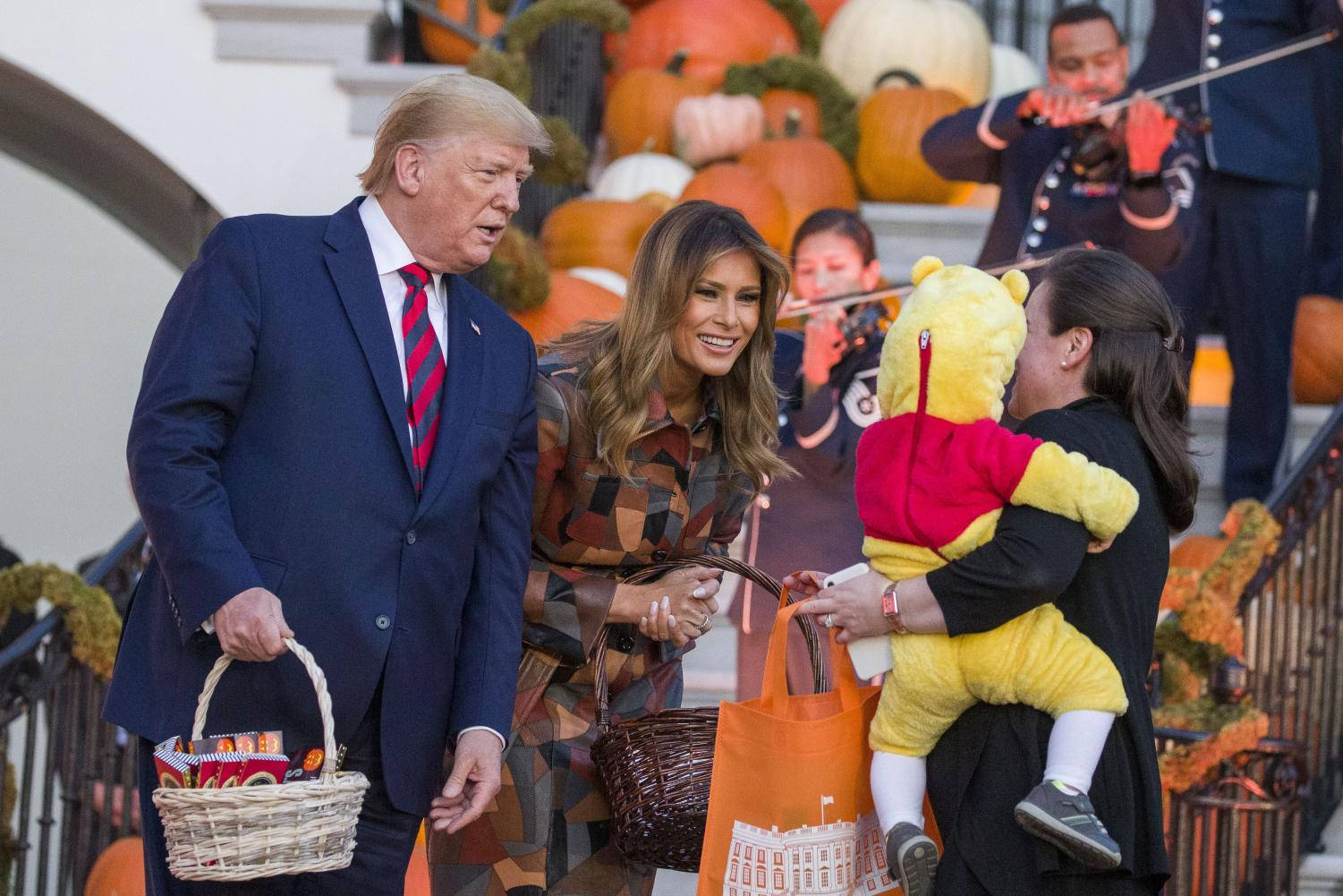 President Donald Trump and First Lady Melania Trump give candy to children during a Halloween trick-or-treat event on the South Lawn of the White House which is decorated for Halloween, Monday, Oct. 28, 2019, in Washington.