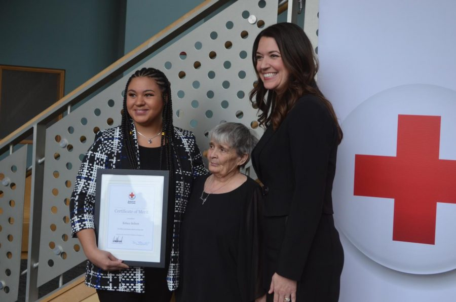 Erica Mani, chief executive officer of the American Red Cross, presents Kelsey Seibert with the Certificate of Merit award for saving the life of Patricia Trippet.
