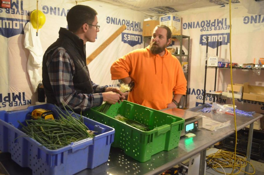 Adam Hudson, director, and Patrick Bradshaw, crew chief, discuss order loads of fresh produce.