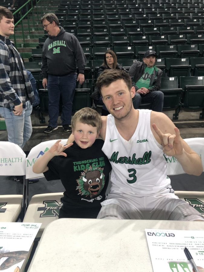 Ben Hively posed with Herd men's basketball player Jannson Williams after a basketball game at the Cam Henderson Center.