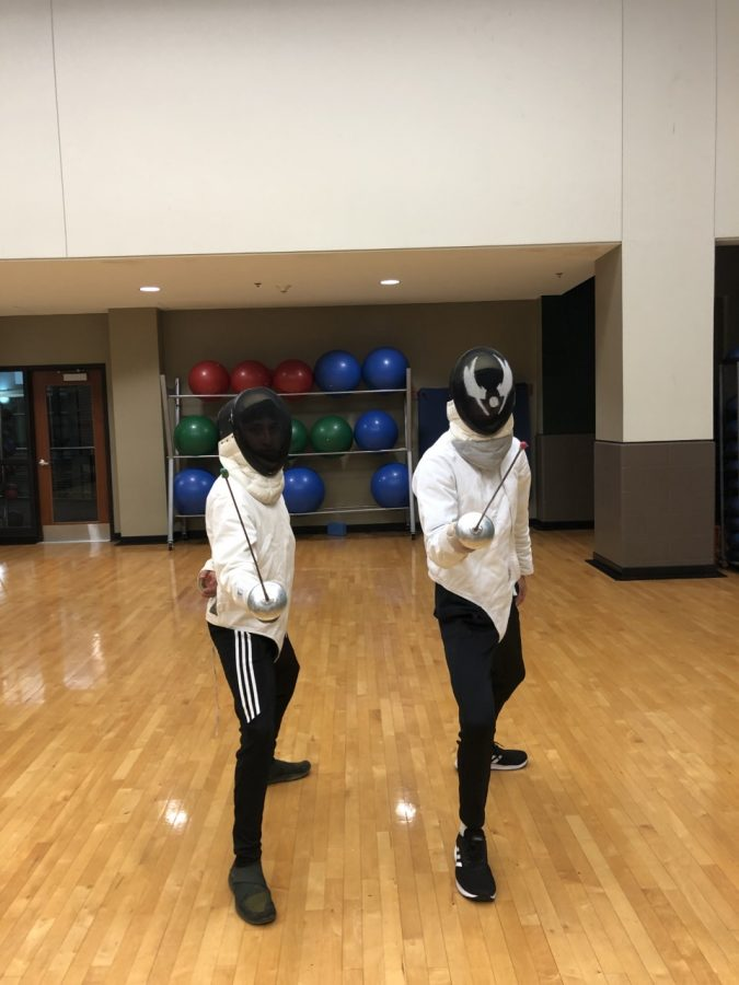 Marshall University Fencing Club members Elijah Vela and Scott Cooper show off fencing gear and pose.