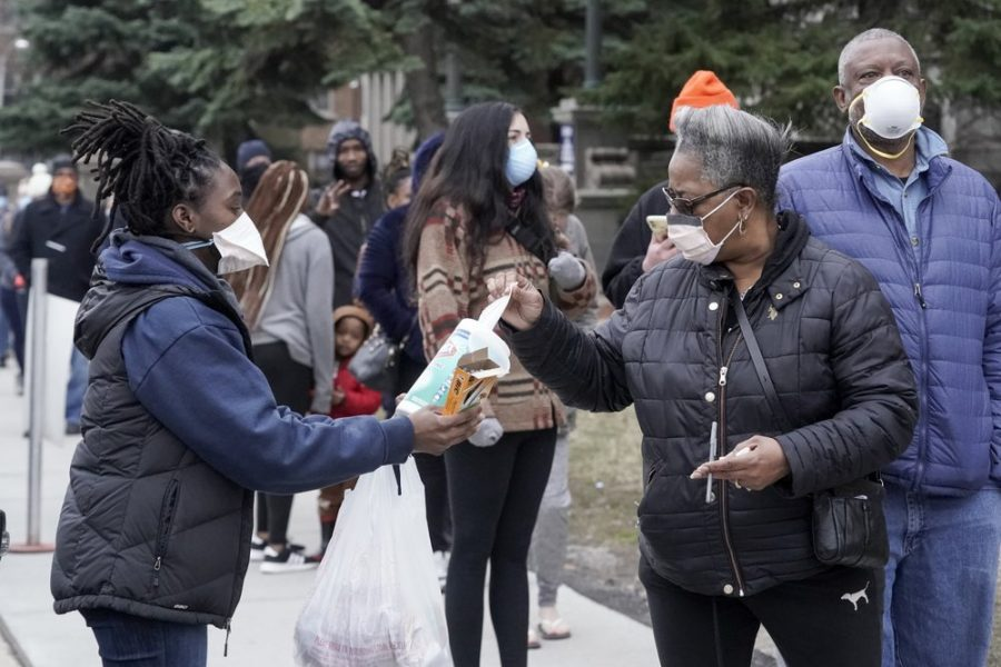 A worker hands out disinfectant wipes and pens as voters line up outside Riverside High School for Wisconsin's primary election Tuesday, April 7, 2020, in Milwaukee.