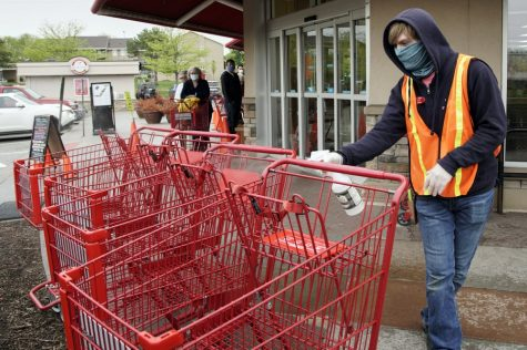 Dilon Moore disinfects shopping carts and controls the number of customers allowed to shop at one time at a Trader Joe's supermarket in Omaha, Neb., Thursday, May 7, 2020. Store workers across the country are suddenly being asked to enforce the rules that govern shopping during the coronavirus pandemic.