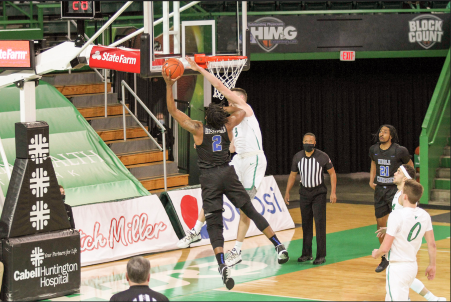 Senior Jannson Williams reaches to block a shot on the night he set the Marshall all-time blocks record.