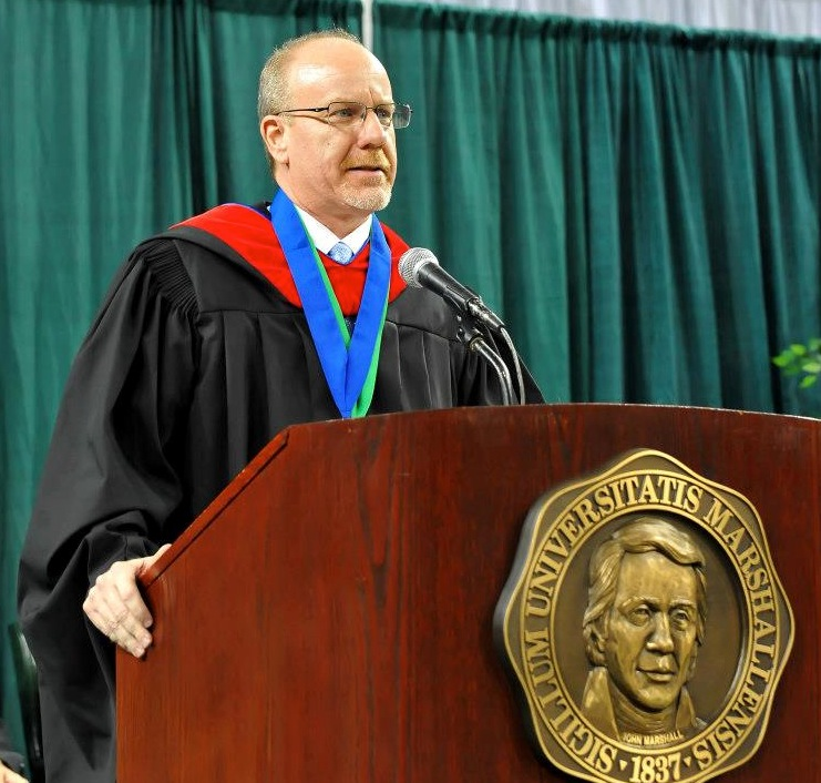 Professor Dan Hollis speaking at Marshall University graduation event.