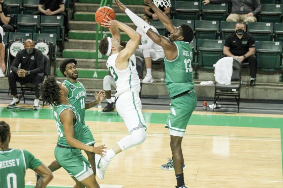 Jarrod West takes the ball strong to the rim against North Texas defender Thomas Bell during Friday, Feb. 26's contest with the Mean Green.